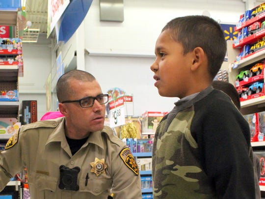 Luna County Sheriff's Deputy Robert Nordorf helped Jose Alaniz select a Christmas gift during a past Shop With a Cop event held at the Deming Walmart.
