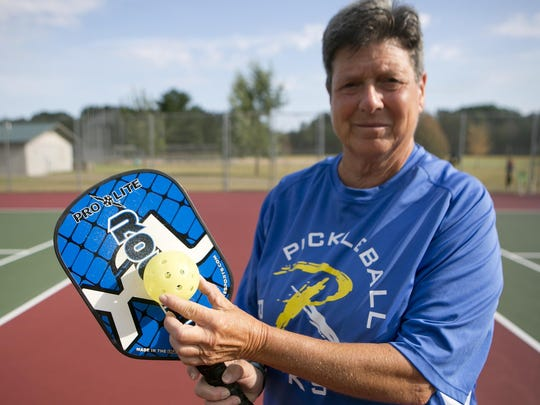 Marcy Mirman poses with a pickleball paddle and pickleball at Little Plover River Park on Thursday, Aug. 6, 2015.