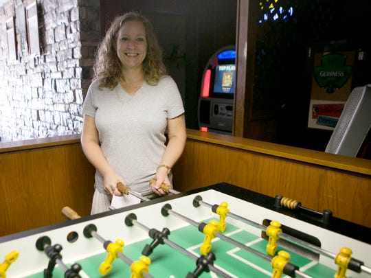 Bar manager Jen Lukaszewski poses with the foosball table at Mulligans Irish Pub in Wisconsin Rapids, Thursday, Sept. 3, 2015.