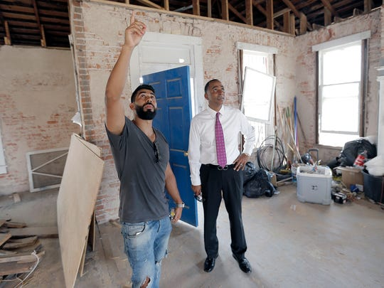Johnny Escalante, left, last week showed Renard Johnson work being done in a home at 109 N. Coldwell that he's converting to a bar. It's just down the street from the Downtown El Paso baseball stadium. Johnson is building an apartment complex next door to the bar.