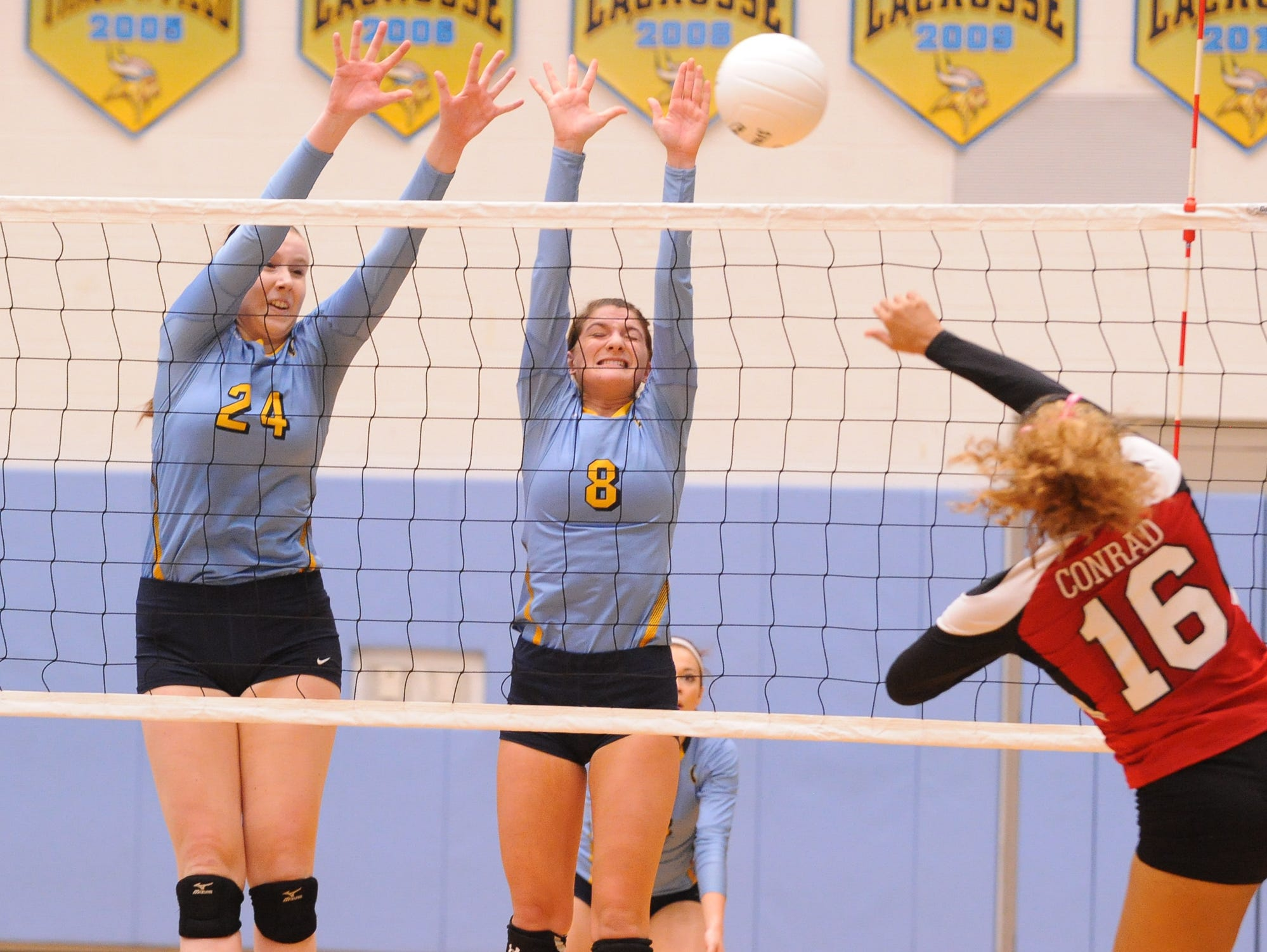 Cape's #24 Abigail E'Nama and #8 Taylor Collier jump up for the ball in the third game against Conrad Thursday night at Cape Henlopen High School.