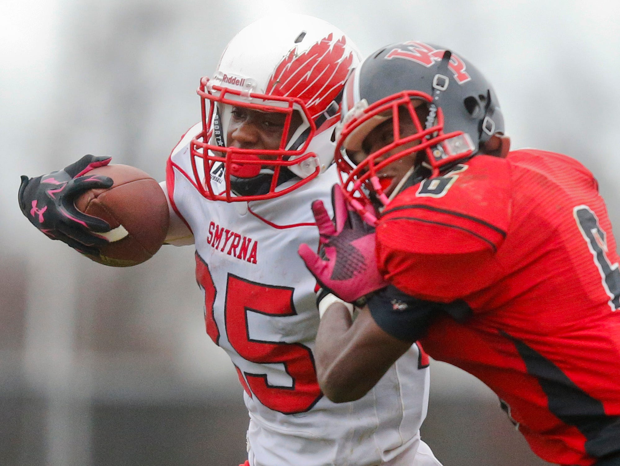 Smyrna's William Knight tries to get past William Penn's Kamau Floyd on a fourth quarter scoring drive during Smyrna's 30-13 win in a semifinal of the DIAA Division I state tournament at Bill Cole Stadium Saturday.