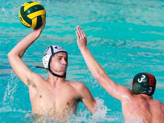 Carston Burgess takes a shot at goal while being defended by Porterville's Steven Wilson during the Central Section Division II championship water polo match at Granite Hills High School in Porterville.