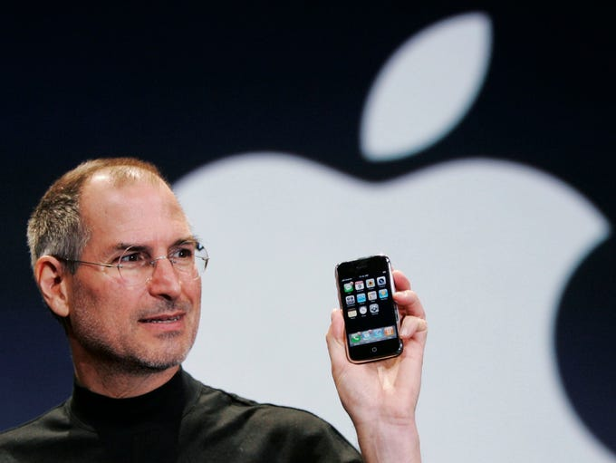 Apple CEO Steve Jobs holds the first generation iPhone