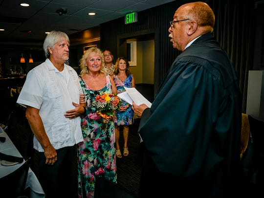 District Court Judge Hugh B. Clarke Jr., right, performs the wedding of Jon Getchel and Sue Quinn Palin Wednesday July 27, 2017 at the Knight Cap Restaurant in Lansing.