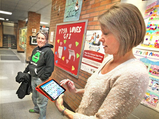 Kindergarten teacher, Mardina Blake (right), at Indianapolis Public School No. 27, loves her new iPad purchased with funds raised by the Can Lady, Mary Stumpp (left), with cashed earned with recycled aluminum cans, red Solo cups, and plastic growler lids.
