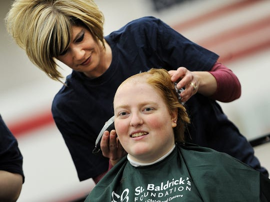 Therese Smit, of The Looking Glass, shaves the head of Taima Kern, of Fond du Lac, at the annual St. Baldrick's head shaving event and fundraiser at Fond du Lac High School on Sunday, March 10, 2013.