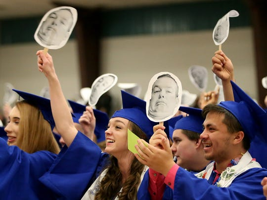 Photos of school resource officer Sheriff Deputy Mark McVey are waved in the air by graduates as he takes the podium during the Olympic High School Class of 2018 graduation ceremony at the Kitsap Sun Pavilion on Thursday.