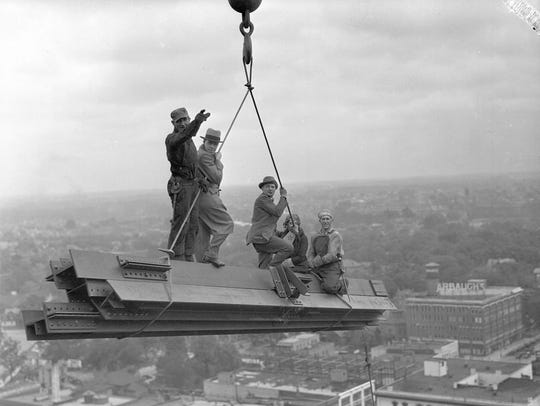 Men ride steel beams above the Lansing skyline as they