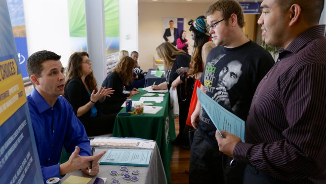 Job seekers talk to recruiter Todd Zedicher of Integrated Life Choices, left, at a job fair in April at Kaplan University in Lincoln, Neb.