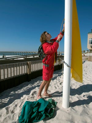 Pensacola Beach Lifeguard, Elis Hines, changes the surf warning flags to green before starting his shift at Casino Beach Tuesday morning March 22, 2016.