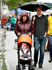 Danielle and Justin Carroll, of Springettsbury Township, push their daughter Ella Carroll, 1, in her stroller as rain drizzles down during Go Green Day in York City, Saturday, April 22, 2017. Dawn J. Sagert photo