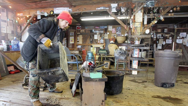 Mary Ellen Resek, who works in the Rabbit Hash General Store, sorts through items salvaged from the 184-year-old store that was  heavily damaged by a fire Saturday. The town's historical society hopes to re-open the store in the town barn dance hall where Resek is working.