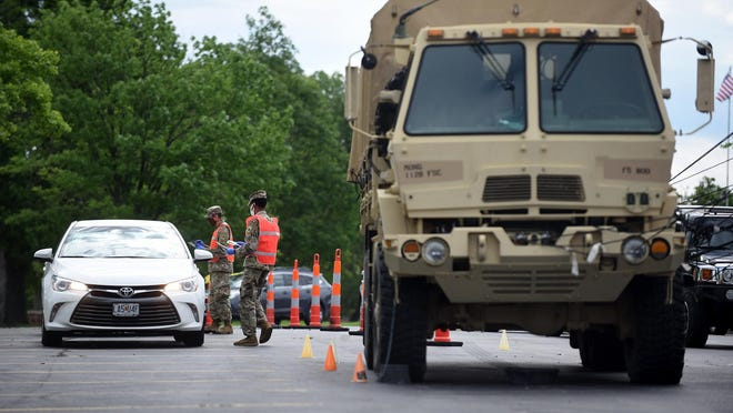 Members of the Missouri Air National Guard and Missouri National Guard test people for COVID-19 at a drive-up testing facility at Hickman High School on Monday. The testing site will be open on Tuesday from 7 a.m. to 7 p.m. Drivers are to enter the school parking lot at Providence and Forest Avenue and follow the signs.