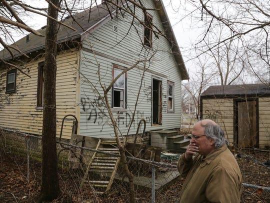 Harold J Skinner shows the back of the vandalized abandoned