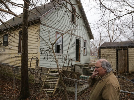 Harold J Skinner shows the back of the vandalized abandoned house from his backyard that has sat next door for five years on the city's west side on Monday March 15, 2016.