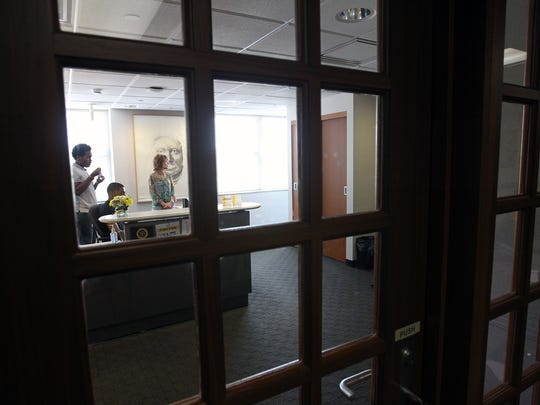 Employees sit behind closed doors at the office of