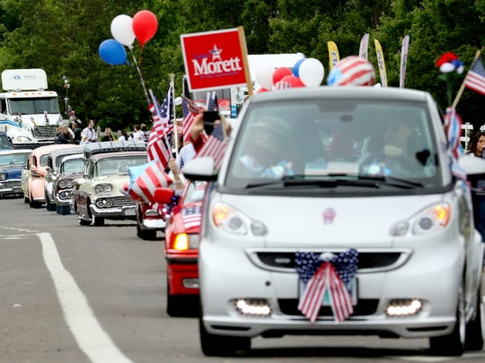 """A """"train"""" of vintage cars and election mobiles wind their way through Keizer for the Iris Festival Parade on Saturday, May 21, 2016."""
