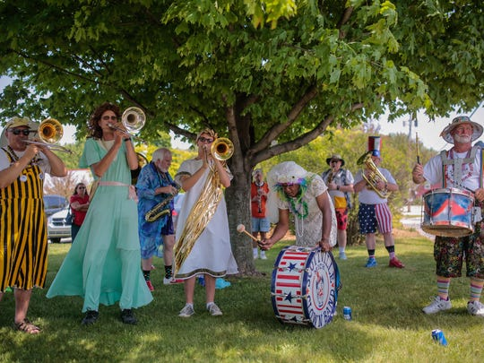 Members of the Scottville Clown Band warm up while waiting for their turn to march and play in a parade during the National Asparagus Festival in Hart, Mich., on  June 11, 2016.