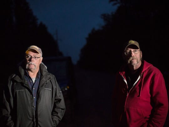"""It's impressive to see what people think is a phenomenon,"" said Terry Nestle (left), 65 of Ithica, while standing with Rick Michael, 61, of Midland, in the darkness off of Robbins Pond Road in Paulding, Mich., where they'd come to see the legendary Paulding Light for the first time. ""I wouldn't lose any sleep over wondering what it was, but to see it now, yeah it's cool,"" Michael said."