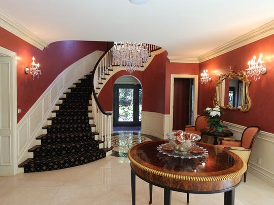 Beyond that is a glamorous foyer they created by taking out walls, adding a marble floor with a large marble medallion they designed and a grand crystal chandelier.