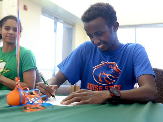 Ahmed Muhumed signs a letter of intent to be on the cross country team at Boise State University during a signing day ceremony for eight student athletes at West Salem High School on Wednesday, Nov. 9, 2016.