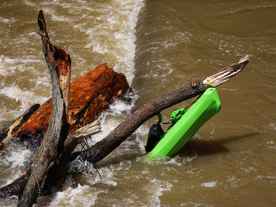 "A kayak remains jammed in debris near the Broad Ripple dam of the White River at Westfield Boulevard and 72nd Street, where the river passes below the Monon Trail in Indianapolis, Sunday, July 9, 2017. Two kayakers were in critical condition after being rescued from the ""boil,"" a rapid churning area of the low-head dam. The force of the water pulled off the life vests that both kayakers had been wearing."