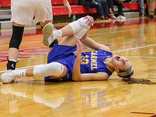 Carmel Greyhounds guard Amy Dilk (10) grimaces in pain as she injured her knee during semifinals against the Noblesville Millers at Fishers High School in Fishers, Ind., Friday, Feb. 2, 2018. Dilk returned to the game and Carmel won, 50-45.