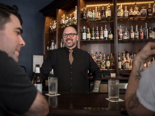 Bartender Rick Paulger, center, talks to Nick Chapman,