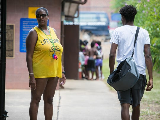 Glenda Pinkett, pool manager at Dr. Foster M. Brown Pool in Wilmington, stands by the entrance gate as another lifeguard arrives for duty.