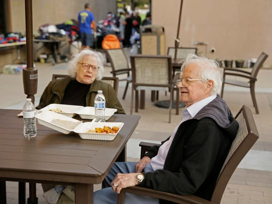 FILE - In this Oct. 11, 2017 file photo, wildfire evacuees Jim Merriman, right, and his wife Lu have a meal while spending the evening at a Red Cross disaster relief center in Santa Rosa, Calif. The vast majority of those who died in the Northern California wildfires were in their 70s and 80s including several couples who died together. (AP Photo/Eric Risberg, File)