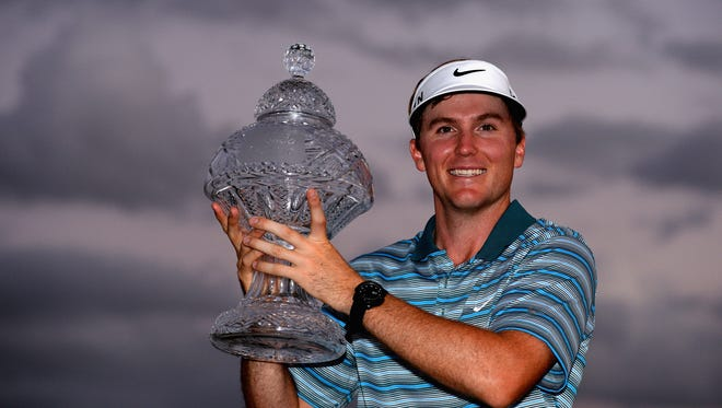 March, 2, 2014 - Russell Henley celebrates with the trophy after winning The Honda Classic at PGA National Resort and Spa in Palm Beach Gardens, Florida.