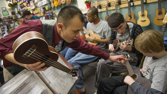 "Samson Trinh shows proper finger placement to Tadhg Leahy, 9, during his ?Uke 'n' Roll"" ukulele on Jan. 19 in Richmond, Va."