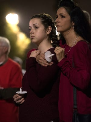 Sabrina Lawyer and her mother join other in honoring the victims of last weeks school shooting in south Florida during a ceremony at East Brent Baptist Church Monday, Feb 19, 2018.