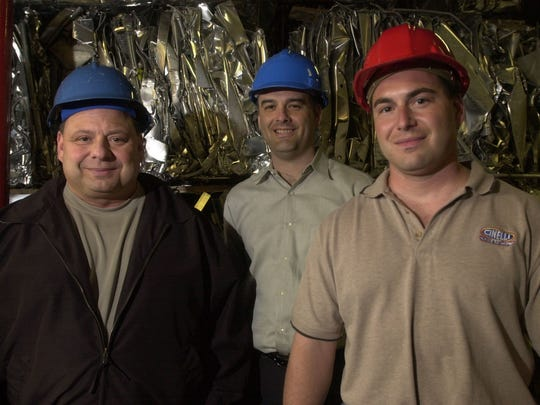 Joe Cinelli, left, president of Cinelli Metal Recycling, and his partners, Dave Barteck, center, and brother, Craig Cinelli on April 29, 2003. Behind them is a bale of crushed metal, which will be melted down to be used again.