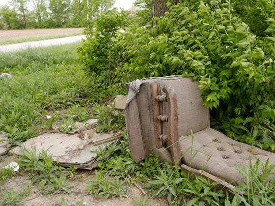 An old recliner is among the discarded items piled off County Road E 150 S Monday, May 14, 2018,  just east of Lafayette.