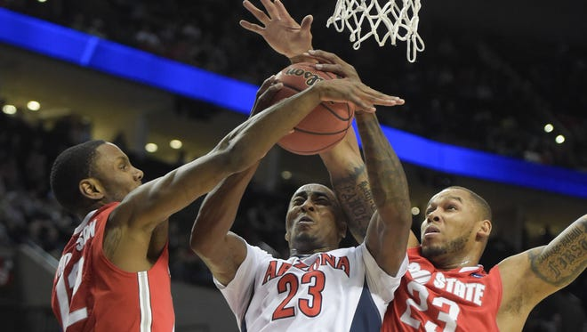 Arizona forward Rondae Hollis-Jefferson is defended by Ohio State forward Sam Thompson (left) and center Amir Williams during the first half Saturday in Portland.