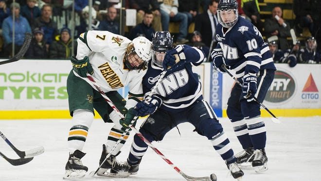 Catatmounts forward Tom Forgione (7) battles for the puck with Wildcats forward Tyler Kelleher (16) during the men's hockey game between the New Hampshire Wildcats and the Vermont Catamounts at Gutterson Fieldhouse on Friday night February 10, 2017 in Burlington.