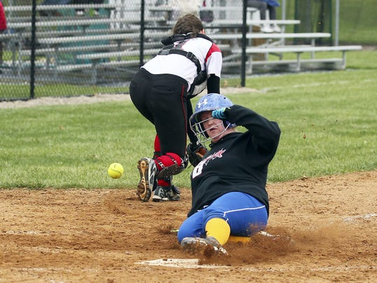Northern Lebanon's Erica Dulac slides in safely at home plate as Annville-Cleona catcher Amber Rexrode retrieves an errant throw.
