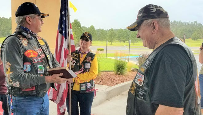 Terry Proctor, who will take the flag to Clovis, listens to Keith Reeves, at left, reading the Nation of Patriots oath.