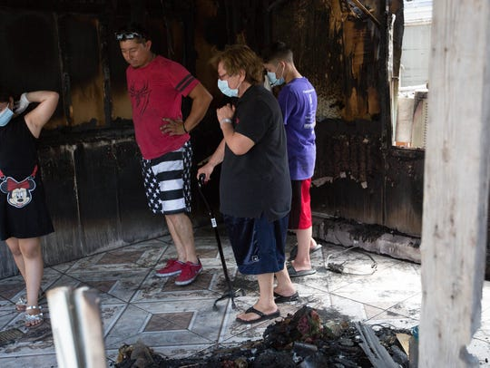 Zenaida Ochoa, center, is escorted through the burned