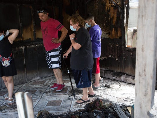 Zenaida Ochoa, center, is escorted through the burned remains of her mobile home by her grandchildren, who helped to remove salvageable items on Thursday July 5, 2018.