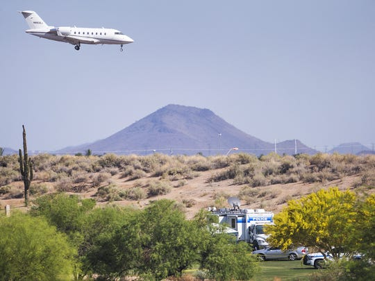 A jet makes final approach to Scottsdale Airport, Tuesday, April 11, 2018. Police vehicles and yellow tape below surround the site of a Piper Comanche that crashed near the second hole of the Champions course at TPC Scottsdale Monday night, killing all six on board.