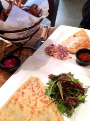 A spinach and feta crepe and a Johnny crepe with pulled pork, caramelized onions, cheddar cheese and barbecue sauce, and sweet potato fries at the Skinny Pancake on the Burlington waterfront in 2014.