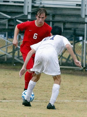 Center Grove's Hayden Gorall takes on a Bloomington South defender in the Trojans' 5-2 semistate win last week.