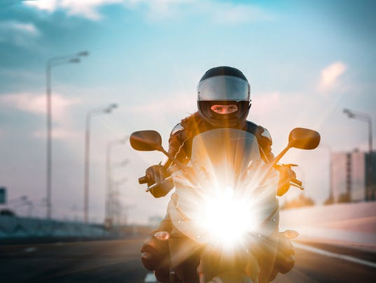 Woman drives on a motorcycle on a morning highway