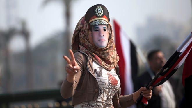 An Egyptian woman wears a mask of Egypt's Defense Minister Abdel Fattah el-Sissi in Tahrir Square.