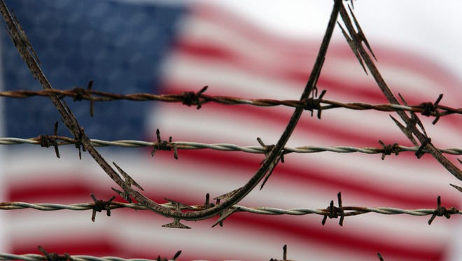 An American flag flies behind the barbed and razor-wire at the Camp Delta detention facility, at Guantanamo Bay U.S. Naval Base, Cuba.