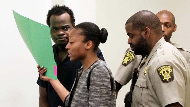 Basil Eleby is escorted by his public defender and two Fulton County Sheriff's office officers into the court room at the Fulton County Jail in Atlanta  on Saturday where he was charged with arson in connection with an Atlanta bridge fire.