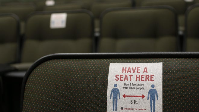 Stickers mark seats that students should avoid in order to social distance inside a large Miller Learning Center Class room on the first day of the fall semester on Thursday, August 20, 2020.